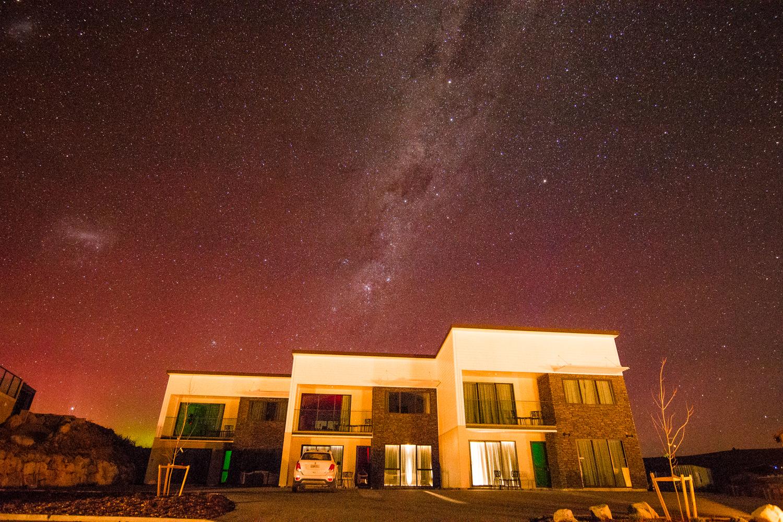 Aurora and milky way imagine behind the Tekapo Luxury Apartments in Lake Tekapo New Zealand